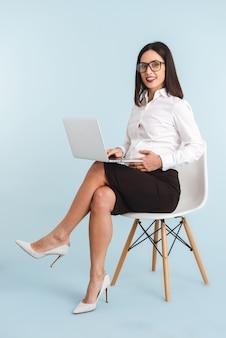 Photo d'une jeune femme d'affaires enceinte isolée à l'aide d'un ordinateur portable.