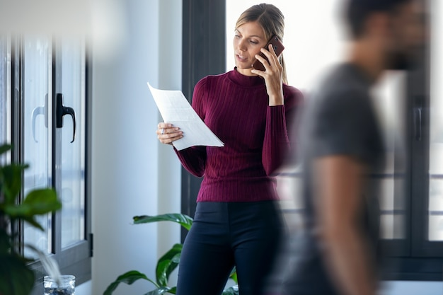 Photo d'une jeune femme d'affaires prospère au travail parlant sur un téléphone portable et lisant des documents tout en se tenant près de la fenêtre du bureau.