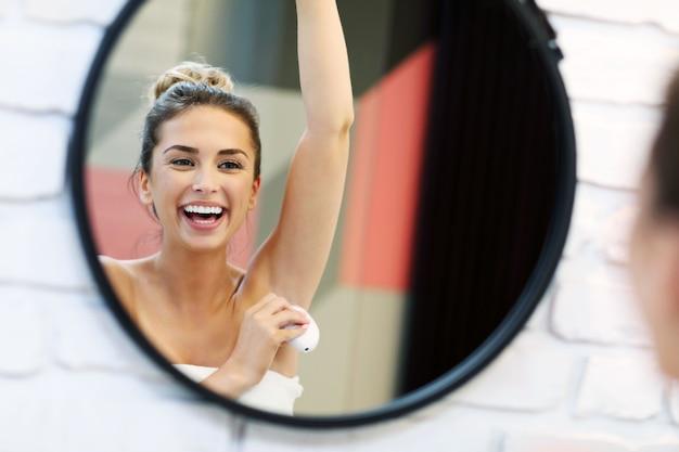 Photo de jeune femme à l'aide de déodorant dans la salle de bain
