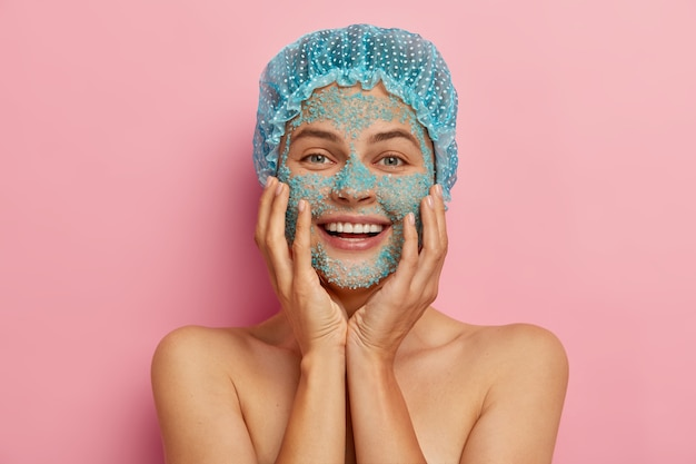 Photo d'une jeune femme à l'air agréable se soucie de la peau, applique des granules de sel de mer sur le visage, a l'air rafraîchie et heureuse, se tient seins nus contre le mur rose, prend plaisir à rajeunir