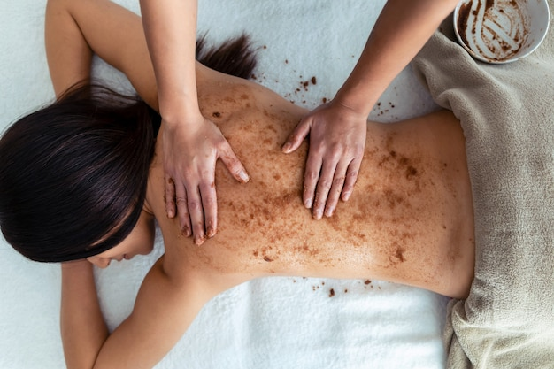 Photo d'une jeune femme appliquant une crème au chocolat avec des ingrédients naturels pour un traitement corporel à une jolie femme au centre de spa.