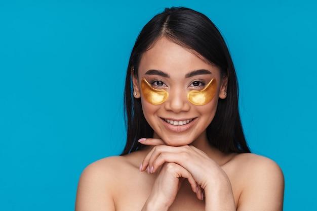 Photo d'une jeune femme asiatique optimiste positive et heureuse posant isolée sur un mur bleu, prenez soin de la peau sous les yeux avec des patchs.