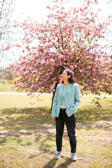Une photo d'une jeune femme assise au milieu de la nature et souriante en profite
