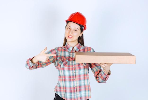 Photo de jeune femme au casque rouge tenant une boîte en carton et pointant du doigt.