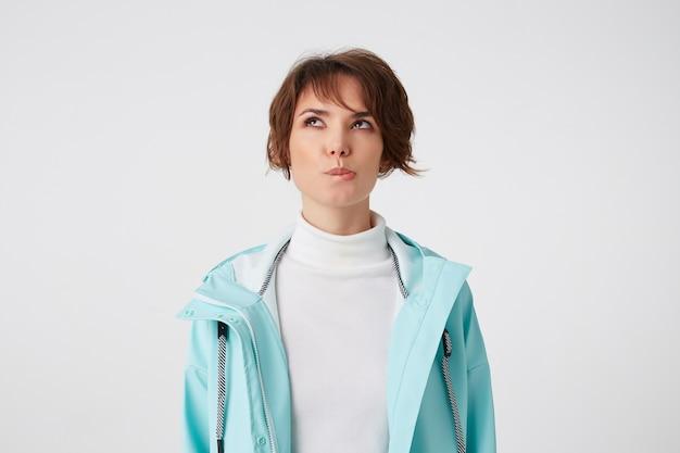 Photo de jeune femme aux cheveux courts pieux en golf blanc et manteau de pluie bleu clair, mord les lèvres et lève les yeux, se dresse sur fond blanc.