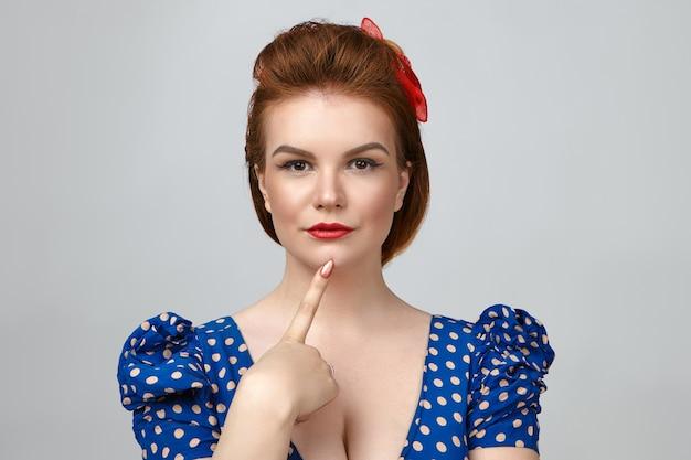 Photo de jeune femme aux cheveux rouges glamour à la mode habillée en style pin up posant isolé en studio, tenant le doigt sur son menton et regardant la caméra avec un regard pensif pensif