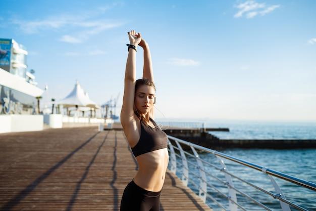 Photo de jeune femme belle remise en forme fait des exercices de sport avec la côte de la mer sur le mur