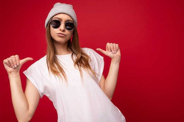 Photo d'une jeune femme blonde foncée attrayante et positive avec des émotions sincères portant un blanc décontracté