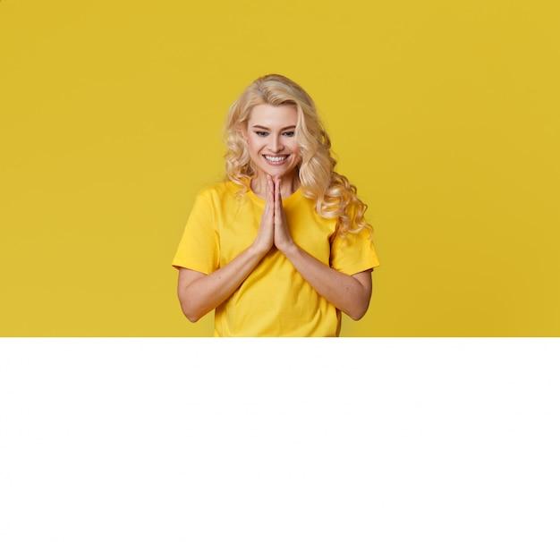 Photo d'une jeune femme blonde heureuse debout isolé sur mur jaune