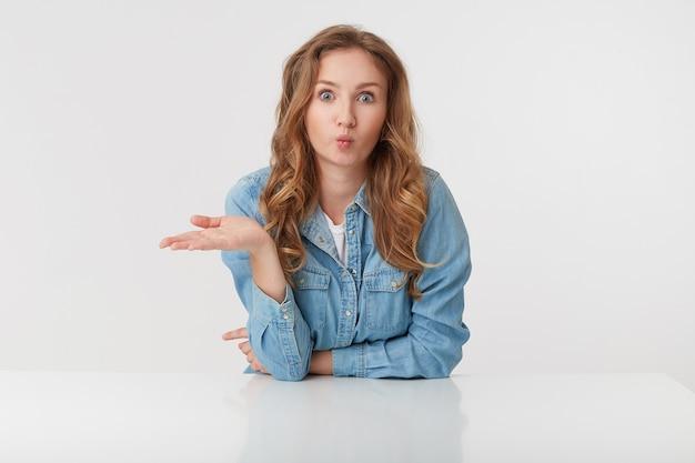 Photo de jeune femme blonde mignonne porte des chemises en jean, assise à la table blanche et envoie un baiser, a l'air heureux et joyeux, isolé sur fond blanc.