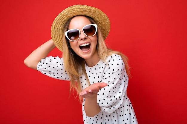 Photo d'une jeune femme blonde souriante assez positive portant un chapeau de paille en robe d'été