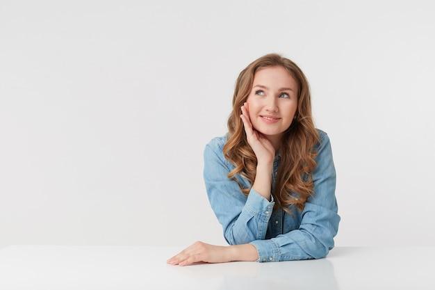 Photo de jeune femme blonde souriante porte des chemises en jean, assis à la table blanche, rêvant et a l'air heureux, isolé sur fond blanc.