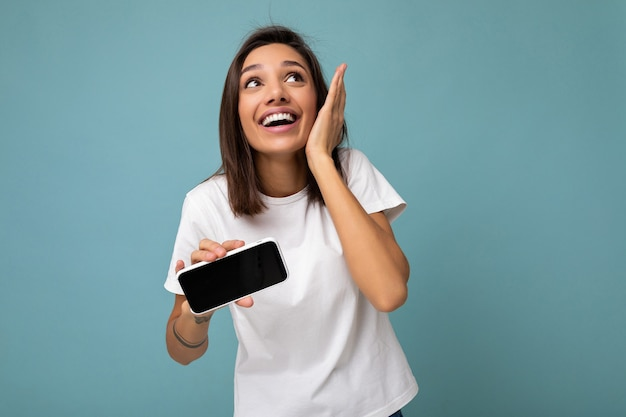Photo d'une jeune femme brune étonnée assez positive à la belle portant un t-shirt blanc debout