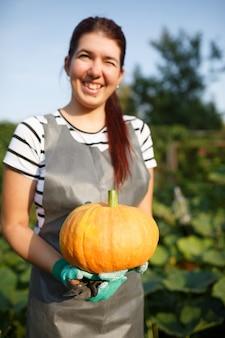 Photo de jeune femme avec citrouille dans les mains au jardin le jour d'été