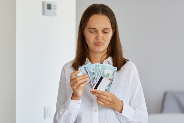 Photo d'une jeune femme confuse et bouleversée portant une chemise blanche tenant de l'argent et une carte de crédit, regardant des billets de banque, n'a pas assez d'argent pour acheter un achat de rêve.