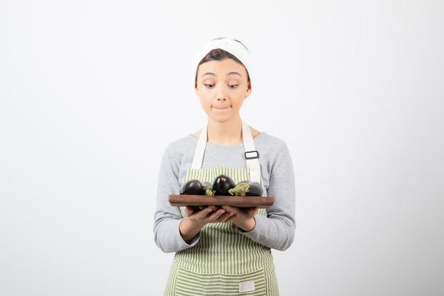 Photo de jeune femme cuisinier regardant une assiette d'aubergines sur blanc