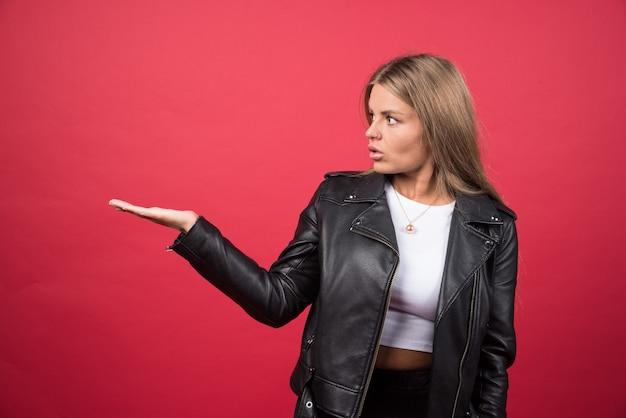 Photo d'une jeune femme debout et montrant copyspace