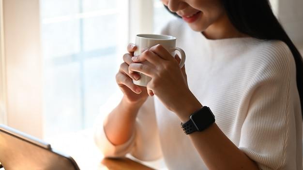 Photo d'une jeune femme designer tenant une tasse de café dans ses mains alors qu'elle était assise à la table de travail moderne après avoir fini de concevoir un nouveau projet. concept de détente / pause après le travail.