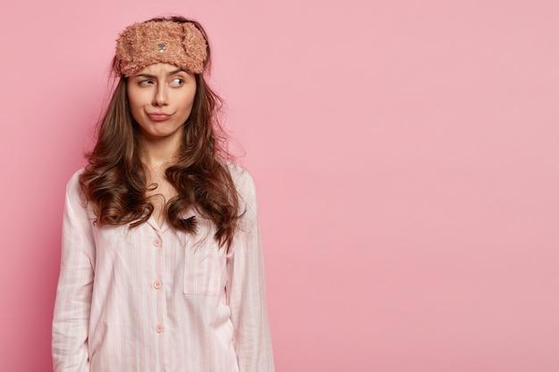 Photo d'une jeune femme détendue et réfléchie a les cheveux bouclés, porte un masque pour les yeux, une combinaison de nuit, concentrée sur le côté, pose sur un mur rose avec un espace libre pour votre contenu promotionnel. concept de l'heure du coucher