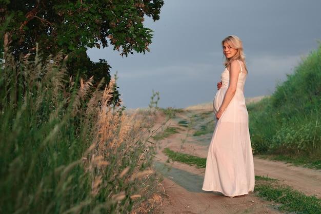 Photo de jeune femme enceinte en élégante robe blanche élégante posant dans le parc contre le ciel sombre. bannière horizontale
