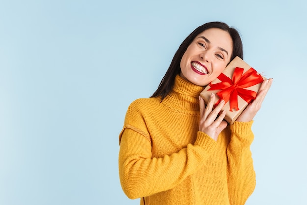 Photo d'une jeune femme enceinte isolée tenant une boîte-cadeau.