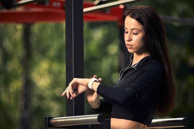 Photo d'une jeune femme européenne sur une séance d'entraînement de rue dans un parc sportif par une journée ensoleillée. concept de formation en plein air.