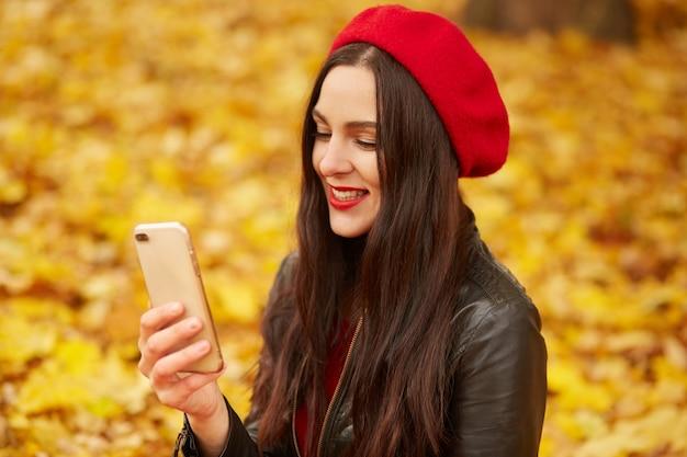 Photo de jeune femme faisant selfie ou ayant un appel vidéo dans le parc automne. belle fille robes redberet