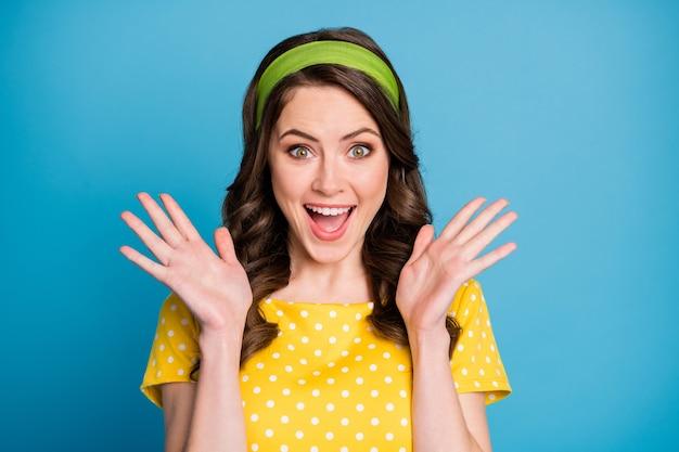 Photo d'une jeune femme folle et étonnée crier fort lever les mains porter des vêtements à pois isolés sur fond de couleur bleu