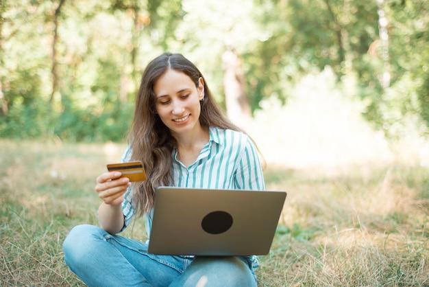 Photo de jeune femme heureuse faisant des services bancaires en ligne sur ordinateur portable avec carte.