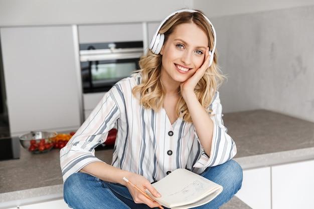 Photo d'une jeune femme heureuse à l'intérieur de la cuisine, écoutant de la musique avec des écouteurs en écrivant des notes.