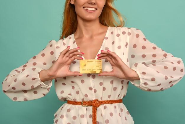 Photo de jeune femme heureuse posant isolée sur fond de mur bleu tenant une carte de débit ou de crédit.