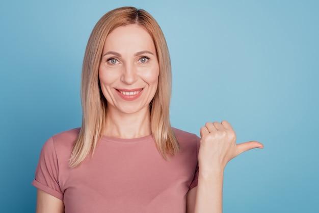Photo de jeune femme heureuse sourire positif indiquer l'espace vide du pouce ad promo conseil choix isolé sur fond de couleur bleu