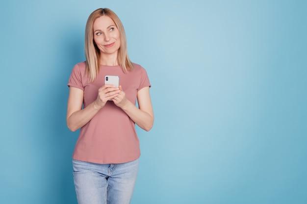 Photo de jeune femme heureuse sourire positif utiliser téléphone portable rêve regarder espace vide isolé sur fond de couleur bleu