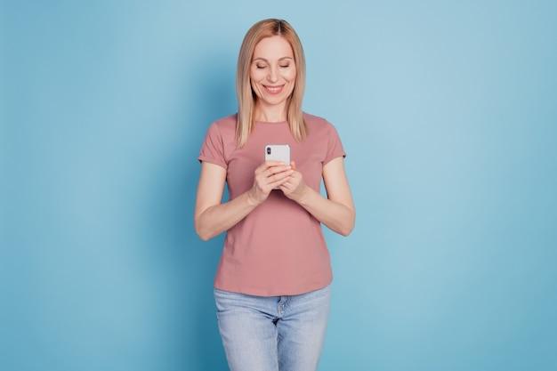 Photo de jeune femme heureuse sourire positif utiliser le type de chat de téléphone portable sms en ligne isolé sur fond de couleur bleu