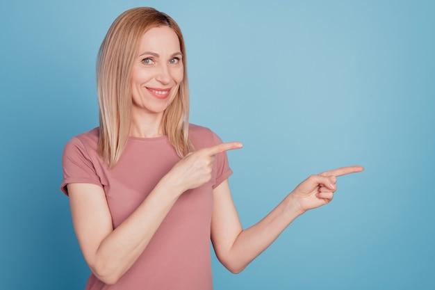 Photo de jeune femme heureux sourire positif indiquer doigts espace vide sélectionnez suggérer publicité isolé sur fond de couleur bleu