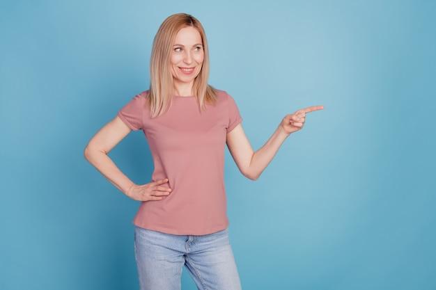Photo de jeune femme heureux sourire positif look indiquer doigt espace vide promo choisir des annonces isolées sur fond de couleur bleu