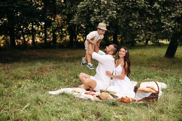 Photo d'une jeune femme et d'un homme de race blanche gaie tenant leur enfant sur les mains, souriant et se réjouissant