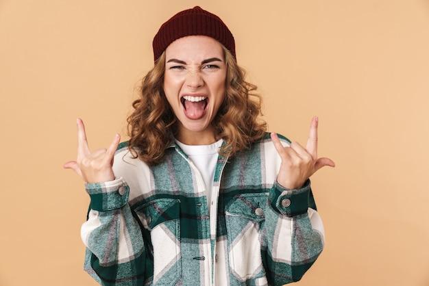 Photo d'une jeune femme impertinente en bonnet tricoté criant et faisant des cornes avec les doigts isolés sur beige