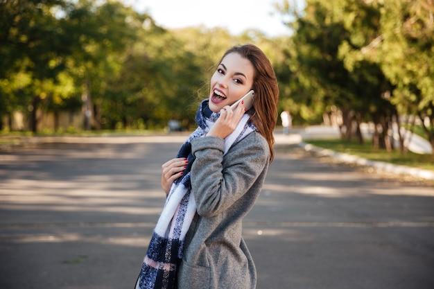 Photo d'une jeune femme incroyable parlant au téléphone portable en regardant la caméra.