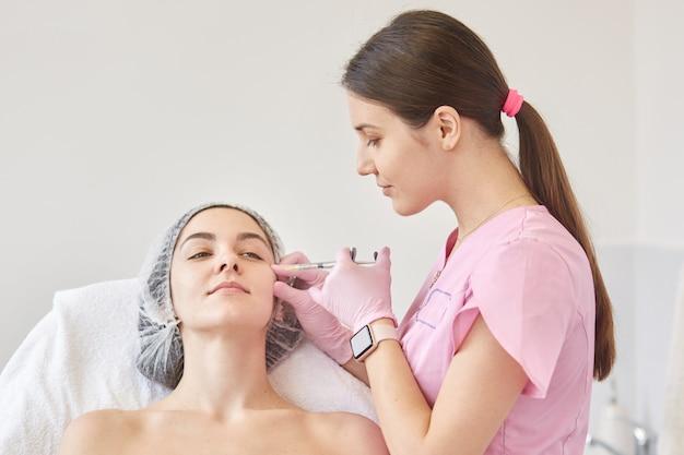 Photo d'une jeune femme injectée de collages sur son visage à la clinique.
