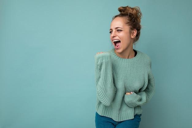 Photo d'une jeune femme jolie blonde joyeuse et joyeuse portant un maillot bleu isolé sur fond bleu avec un espace vide et célébrant la victoire. notion positive.