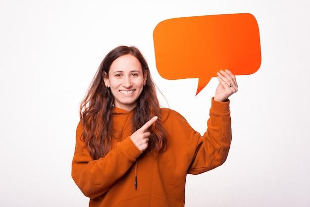 Une photo d'une jeune femme joyeuse tenant une bulle de dialogue et pointe vers elle
