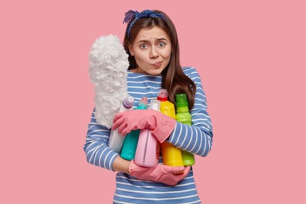 Photo d'une jeune femme malheureuse habillée avec désinvolture, porte une brosse et des détergents, regarde avec une expression inquiète, porte un bandeau