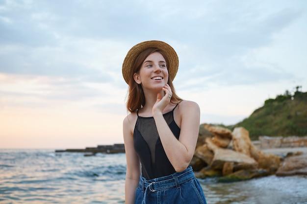Photo d'une jeune femme mignonne au gingembre avec des taches de rousseur se promène sur la plage, porte un chapeau, regarde au loin et touche les fromages, a l'air positif et heureux.
