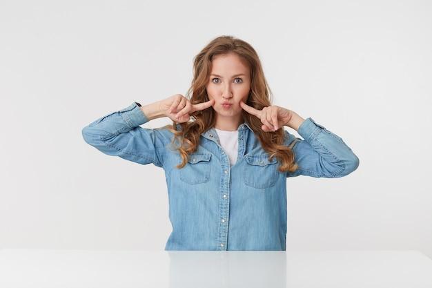 Photo de jeune femme mignonne avec de longs cheveux ondulés blonds en chemise en jean, touche ses joues et souffle les lèvres, a l'air drôle. isolé sur fond blanc.