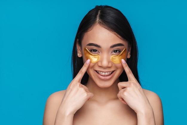 Photo d'une jeune femme optimiste souriante asiatique posant isolée sur un mur bleu prendre soin de la peau sous les yeux avec des patchs.
