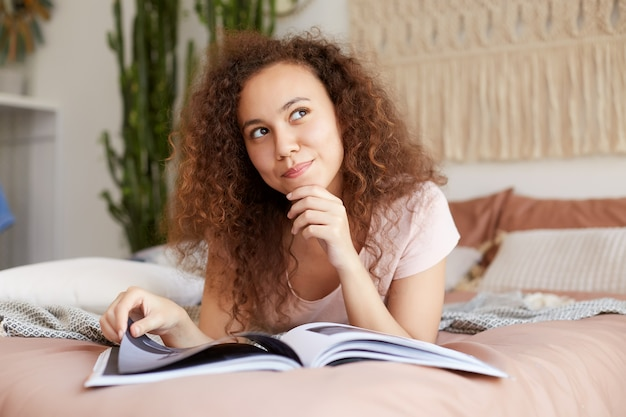 Photo d'une jeune femme à la peau sombre et aux cheveux bouclés, allongée sur le lit et touche le menton, détourne le regard rêveur et sourit.