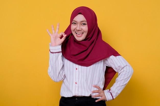Photo de jeune femme portant le hijab disant bon geste, regarde joyeusement l'expression