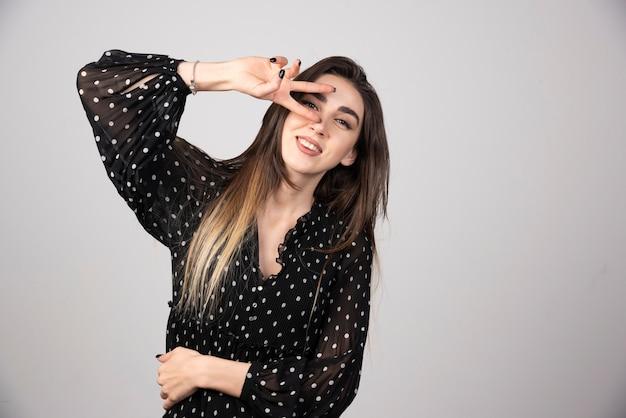 Photo d'une jeune femme portant une robe souriante et montrant un signe de paix.