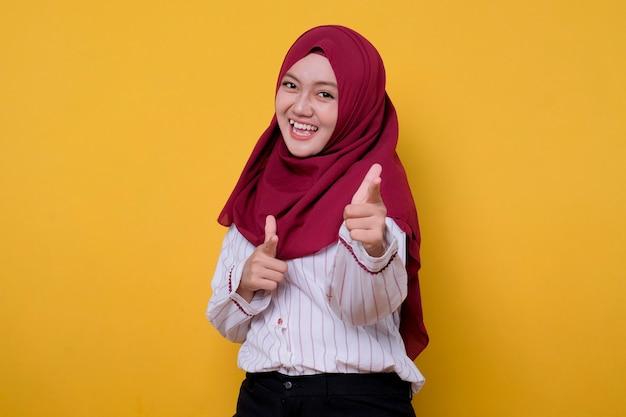 Photo, de, jeune femme, porter, hijab, pointage, geste, regarde, joyeusement, expression